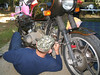 Larry digs into the the ignition in Chris' bike while Chris hides behind the wheel.