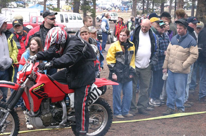 "<font size=""+1"">Back at the start of the ISDE - here's (L-R) a guy on a borrowed XR-650R that won't start (What a way to start a race!) Laura Stephenson, John Stephenson and Tom Stein all watching the festivities with interest and maybe some small amount of sympathy.  Maybe.. </font>"