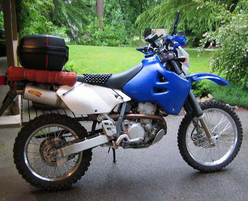 Saddling up the DRZ400-S. The wood bead seat cover makes the stock DRZ seat from painful-after-30-miles  to rideable all day. Amazing. There is a pad of no-slip carpet mesh under the beads to keep them from sliding around. IMS 4.2gal tank. 200 mile range. Givi gear may not look the 'offroad' part, but is very rugged, easy to mount on the ProMoto Billet rack, waterproof, and I already had it.