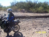 Troy led us along the new approach to the Gila River. The route went down no-name wash to a trail leading to this railroad crossing. The old path up from Donnelly Wash had been barricaded. This was the first time Craig had done extensive wash riding and mentioned that it was a lesson in the value of standing on the footpegs. Jim asked why we didn't tell him to put on his paddle tires. They both must have enjoyed the wash riding though, because when we had the option of leaving the wash and riding the ridge above, both voted to stay in the sand and rode off ahead of me taking the corners like pros. <br /> <br /> We arranged the logs and boards at the RR crossing to ramp us up over the rails. We tried several different methods of crossing the tracks. We all concluded that slowly and carefully is the wrong approach. In the photo above, we had all crossed the tracks and Craig is ready to continue.<br /> <br /> Upon crossing the rails I was in familiar territory and confidently led out on the trail, but I soon found things had changed.  I started following the trail down a dip, only to discover that the rains had washed out a gully in the bottom that was 4 feet deep and 4 feet across. I had to stop on the narrow downward-sloping trail with very little room to turn around and no reverse gear. The other guys helped me back up.  Troy then led us along the cinder beds of the RR tracks to get  around that obstacle.