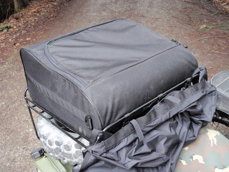 The main bag filled with the inner bags, the top zipped shut, the rain cover is attached to the front of the bag but has not been installed in the full coverage position.