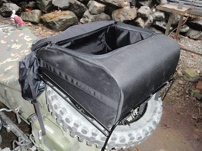 The rain cover can be left attached at the front while the bag is opened to access the interior. This taken from the rear.