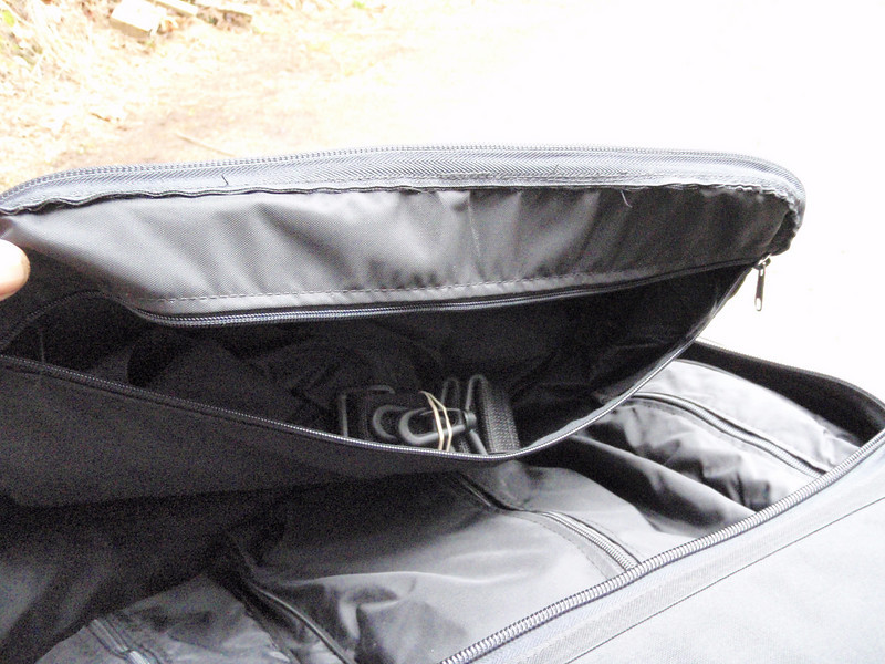 The rain cover and shoulder strap are stored in the top pocket.