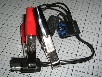 Battery alligator clips allow you to connect to any 12 volt power supply, such as a car battery.  A 15-amp fuse provides protection for the circuit.  The end of the harness has a 2-prong SAE connector that fits the other  accessories of the CyclePump.