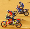 Spanish rider Joan Roma (4) on his KTM overtakes Italian Farizio Meoni 07 January 2003 in their race through Southern Tunisia covering the sixth stage of El Borma in Tunisia and Ghadames in Libya of the current Dakar motor-rallying contest. Roma finished second both in the stage and overall while Meoni stood fourth.