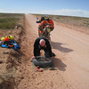 Jay fixing flat tire on road between Hann Flat and Hanksville