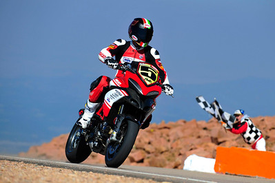 2/9: 2012 -The Ducati Multistrada 1200 S Pikes Peak wins for the 3rd year in succession. Photos courtesy of Ducati Chile The winning riders was Greg Tracy. The track record for bikes of 10 minutes, standing for something like 90 years was broken by Carlin Dunne with a time of 9'52'829 while Tracy also broke the 10 min barrier with a best time of 9'58'262.