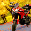 """1/2: Photo (and photoshopping;-) by Canadian Multistrada 1200 owner Bruno L """"<i>Hi Andy this is my 2011 Multistrada 1200S Touring... with some modification.. I paint all the light grey parts in black mat.. colored the Brembo on the front caliper in red .. I have the Pike peak windshield and the third panier on the rear... the picture is taken on a street in Montreal by me.........</i>"""