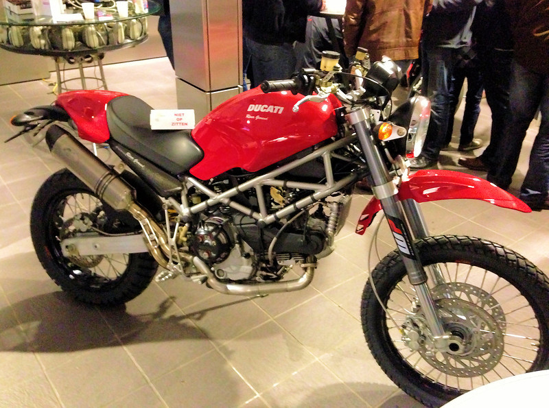 "Ok, not a Multistrada but it is another Ducati that wants to head off road - a moddified Ducati Monster set up for some serious offroad. Thanks to fellow MTS1200 owner JorisM from Holland for the photo: <i> Leo</i> [ Leo Fleuren's of Affetto Ducati - see Leo's MTS1200 Timbuktu Challenge bike <b><a target=""_blank"" href=""http://andyw-inuk.smugmug.com/Motorcycles/Ducati-Multistrada-1200/Multistrada-1200-Timbuktu"">here</a></b>]<i> had a winterproject for another customer who wanted to drive to Timbuktu throught the desert on a Duc. Therefor they build the attached. Perhaps you find this interesting, especially because of the large wire wheels.   If you want something similar .... Leo was talking about bring the bike plus at least € 12k (or did he say 16k? not sure anymore now). One of the major difficulties was the front suspension and the larger wheel - create sufficient space for the wheel to travel without touching the engine or frame. They had to alter the headstock bearings in order to increase the front fork angle by  2 degrees ....   </i>"