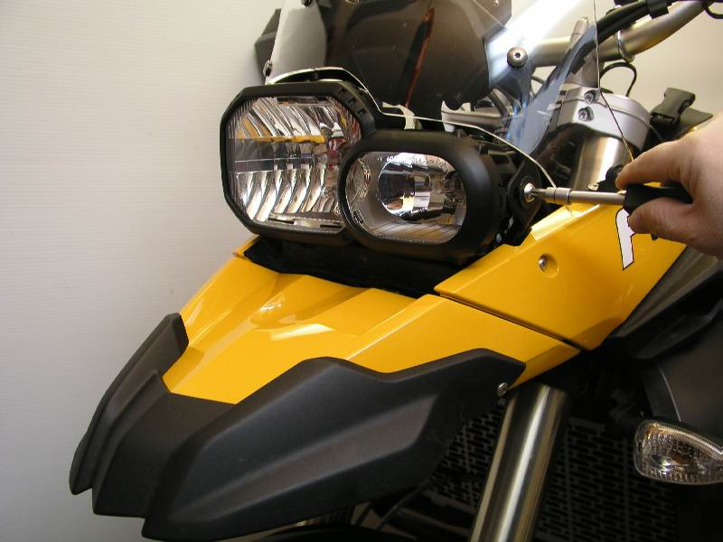 Remove the screw on the side of the headlight.  Do not allow the headlight housing to move or rotate, or your beam pattern will change.  Work on one side at a time.