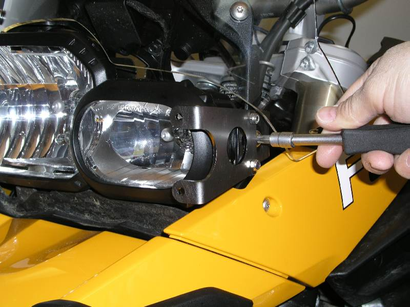 Tightening the screw that holds the bracket to the headlight assembly.