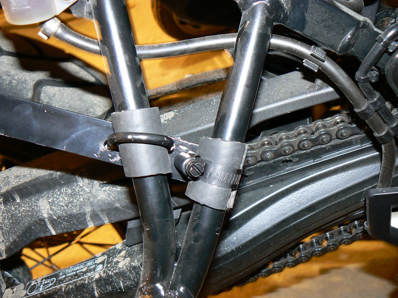 "My own built heat shield and tool tube mounting:<br /> Forward mounting point of tool tube support. ""U"" bracket and pipe clamp both go through the flat alum, rubber tubing placed for grip and protection of passenger peg supports."