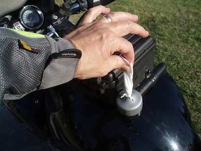 """2.0: I coated a 1 1/4"""" PVC pipe cap with Plasti Dip and cut an """"X"""" in the top of a vinyl boat trailer hub dust cap. Success! The Windex or Pledge Wipe is easy to get to while riding and stays moist for hours. This should also work with a microfiber cloth with Plexus or bug juice in the cap."""