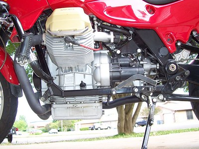 """The bulky stock crossover resided in the space between the oil sump and kickstand. Now the bike has a much narrower """"waist"""" and better growl."""