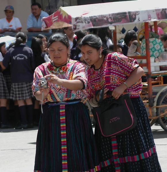 Dos amigas Quetzaltecas, una enseña a otra las fotos de la celebración.  Las ropas tipicas es de Xela.