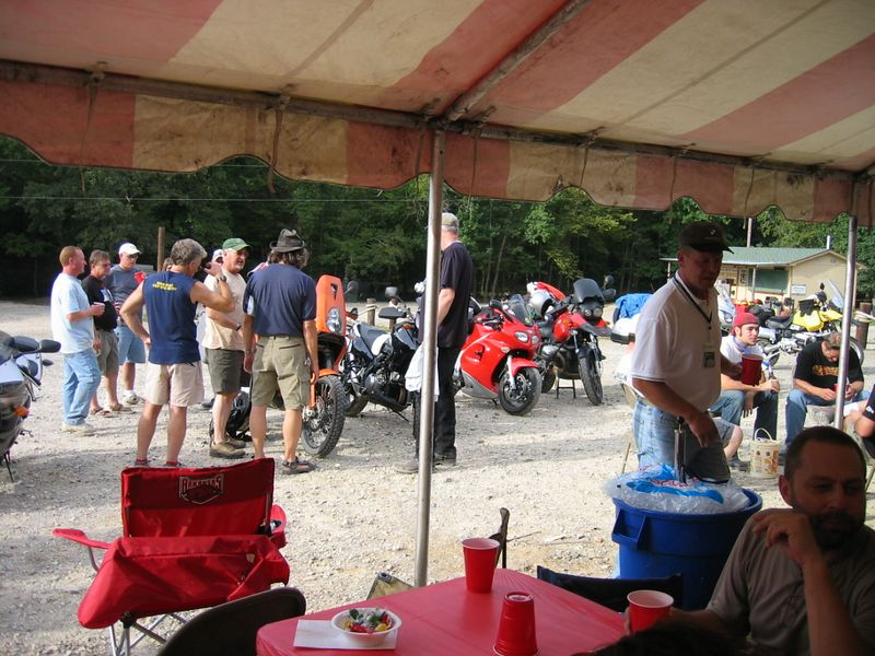 """The big orange KTM was a hit with the homeless hurricane brigade. Jkam, sitting at right, is one of the most famous homeless riders in history. He and Vance organized and financed the shindig as a thank you to all the riders who gave them a place to crash or a meal on wheels during their """"ride the world"""" tour."""
