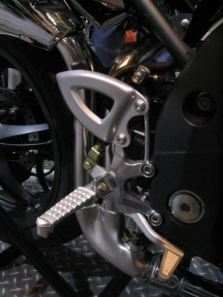 Detail of the Speed Triple pegs.  Wonder how this hardware would look in black?