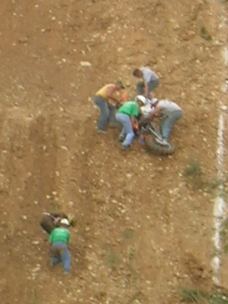 Rider assisted by a safety worker while the rest of the crew holds onto the bike