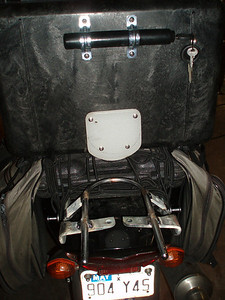 "PELICAN TOP CASE INSTALLATION: The lock is attached to the case with 1"" conduit clamps. I cut a piece off an old plastic cutting board (sorry dear) and bolted it to the case using 1/2"" spacers so as to slide under the front of the U-Bar. Later, I'll make an open luggage rack to attach to the U-Bar bracket. Of course, the whole thing comes off with 4 bolts and the OEM grab bar can go right back on like it never even happened."