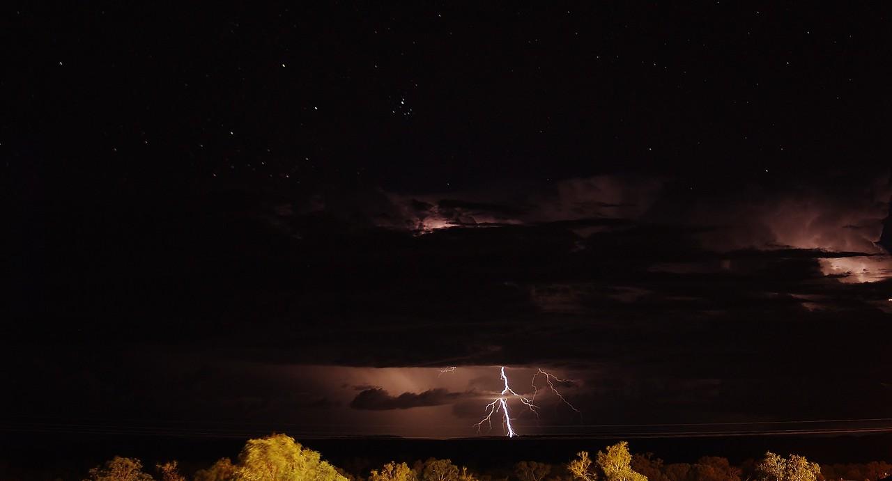 Lightning under a starry sky