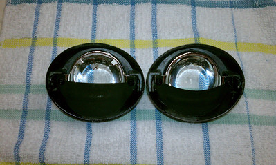 "These Hella Optilux 1100 fog lights suffered from poor assembly as well as design. The lenses were loose and the shields were contorted and out of position so as to crop the light pattern too low. Light was escaping under the shield too. I trimmed about 3/16"" off the bottom of the shields and bent the tabs down on the lens retainer rings to hold the lenses more securely. (Left) BEFORE   (Right) AFTER"