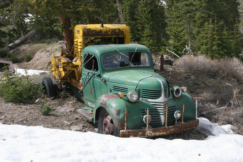 Behind this truck a bucket lays in the snow connected to the winch with a rusty cable.  It's amazing how the trim on the grill still shines after almost 60 years.