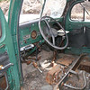 The inside didn't look so good.  I'd guess vandals have pillaged it.  An after market AM radio had been installed just left of the steering wheel.  Notice manual shift and clutch and brake pedals going through the floor board.