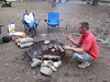 Ron whips up some fine eatin' while another visiting rider Cathy looks on.