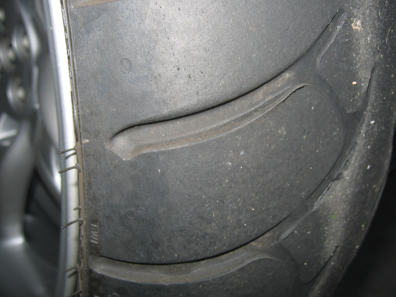 "Look at the sipe nearest the ""TWI"" stamp, and you will see three indicator bars.  You can pretty much ignore the outmost two and focus your attention to the innermost indicator to get a feel for remaining mileage in the tire.  When that innermost indicator is close (say 1/32""), you can consider the tire done."