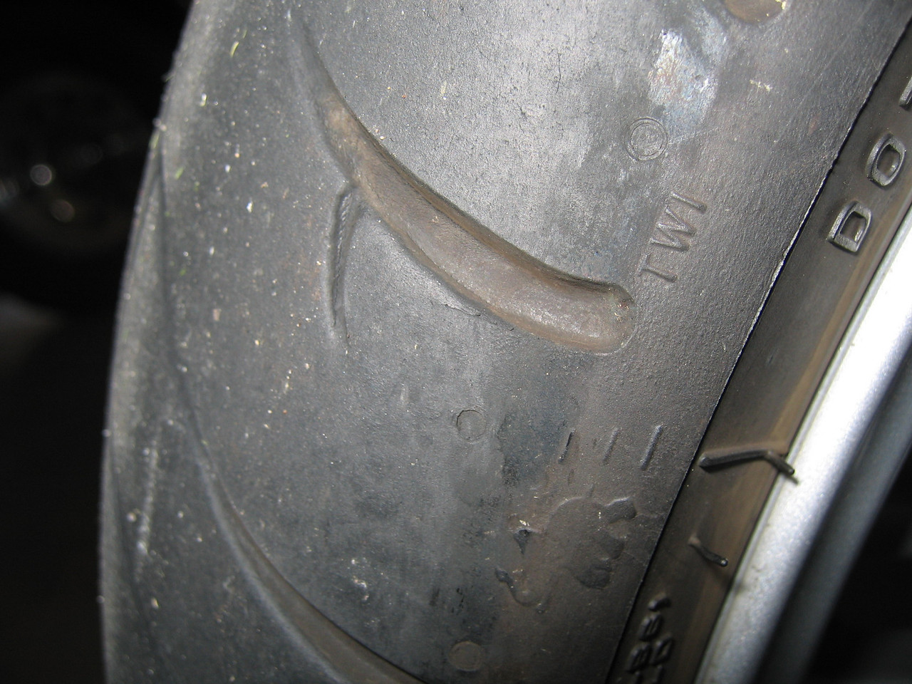 "Look for the ""TWI"" initials on the tire sidewall to locate the wear bars.  TWI = Tread Wear Indicator<br /> <br /> <br /> A kind guest posted this comment:<br /> WARNING: the Metzler Technical Databook reports: ""TWi = Tread Wear Indicator. Identifies those indicators located into the main grooves that appear when the tread depth is reduced to 0,9 mm approx"".<br /> In most european countries tread depth must be at least 1.6 mm."