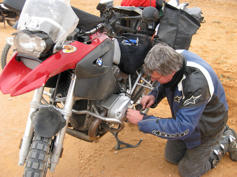 My only off for the trip happened just South of Milparinka. Came over a slight rise doing about 100 kph and hit a 50 metre stretch of loose stuff. Sent me tank slapping and after about 40 metres down I went. Pis weak BMW crash bar folds back onto the cylinder head and puts a crack in it. Never mind Chief Engineer (RAN retired) Dick came to the rescue fixing it with some Liquid Metal which held for the rest of the trip.