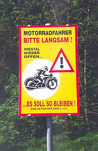 "May 25, 1995 - Wiestal Stausee Road between the Salzburgring race circuit and Hallein, Austria.<br /> <br /> The sign tells it all but I'll translate just in case: ""Motorcyclists, slowly please! The Wiestal is open again (to motorcyclists)... it should remain so"". This road has claimed many sport bike riders that are no longer with us.  The fact that the Salzburgring is right down the road probably doesn't help matters. There are some very tight corners with a rock face on one side and a gorge on the other. Occasionally, the Gendarmerie could be found standing next to their BMW R80s at a rest stop along the road while keeping an eye on drivers."