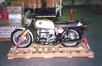 May 08, 1995 - Air Canada Cargo.<br /> <br /> This is my 1980 BMW R65. The pallet was made up from 2 used pallets supplied by the airline company. I supplied the 4x4 lumber to stiffen up the structure as well as the 4 tie down eyes. Tie down straps were on loan from the airline company as well. The paintwork, the instrument pod and headlight were then covered with foam.