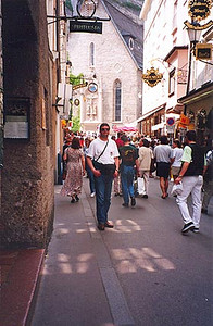 May 26, 1995 - Salzburg, Austria.<br /> <br /> I'm standing in the old part of Salzburg on Getreidegasse with St. Blasius church in the background. The church backs on to the mountain and a short walk to the right will lead you to the Mönchsberg lift, an elevator that runs through the vertical rockface. Once on top, relax and have a few cold ones at Cafe Winkler. The outdoor cafe is situated right on the cliff, providing a excellent view over the city.
