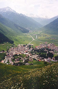 June 12, 1996 - Andermatt, Switzerland.  This is the view of the valley between Andermatt in the foreground and the road leading up to the Furkapass (not visible in the haze) in the background. Just to the West of Andermatt lies the town of Hospental. A turn Southbound  from Hospental leads to the St. Gotthardpass. Further down the valley lies the town of Realp (not visible) that starts at the base of the Furkapass.