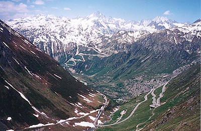 June 10, 1996 - Furkapass, Switzerland.  A view of the West ramp of the Furkapass on the right that leads to the town of Gletsch in the valley below where the road zig-zags up towards the Grimselpass in the background.
