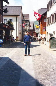 """June 12, 1996 - Andermatt, Switzerland.  This is main street Andermatt, a narrow cobblestone road good enough for one car in some areas; two if you squeeze by in others. Stop by and relax at the """"Hotel 3 Könige & Post"""" for dinner after a long day on the road. You'll meet many motorcyclists that stop by after just coming off the Oberalppass that heads directly into town."""