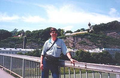 June 11, 1997 - Salzburg, Austria.  I'm standing on Makartsteg, a pedestrian bridge over the Salzach river. In the background on the hilltop; to my right, Bürgerwehr, from where the previous photo was taken, and to my left, Cafe Winkler. An elevator that runs within the vertical rock face can be taken to reach this cafe, otherwise you are looking at a bit of a walk from either side of Mönchsberg. The old part of Salzburg is located on the far side of this bridge. Directly ahead of me, you'll find Mirabellgarten, pictured in the next photo.