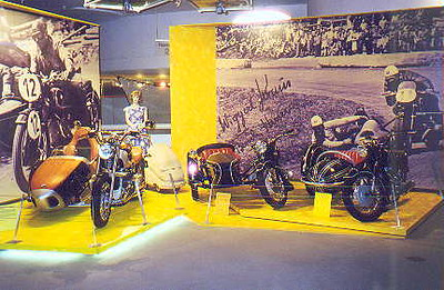June 27, 1998 - BMW Museum, München, Germany.  One of the numerous displays dedicated to the 75th anniversary of BMW motorcycles. A series of BMWs with sidecars. Note the new R1200C with sidecar on the left. The sidecar was nicely finished in wood. Note also the silver coloured BMW kidney grill on the nose of the sidecar.