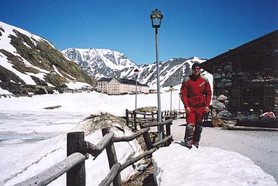June 23, 2001 - Col du Grand St. Bernard, Italy / Switzerland.  The Col du Grand St. Bernard (2469 m asl) lies on the Italian – Swiss border between the towns of Aosta, Italy and Martigny, Switzerland. I'm standing on the Italian side. In the background, Switzerland. Although it was relatively warm and there was a constant flow of water running across the pass road due to rapidly melting snow, the lake to my right was still frozen. The Italian and Swiss border guards standing next to their huts are still in place, but just wave you through.