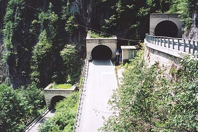 "June 13, 2001 - Passo di San Boldo, Italy.<br /> <br /> Passo di San Boldo (706 m asl) consists of 18 hairpins, of which some of them lie in tunnels. From the north, this pass comes up on you unexpectedly, much like the Maloja Pass in Switzerland when approaching from the east. The road is fairly tame until you reach the other side of the pass, and then, nothing but hairpins. Note the white ""STOP"" line on the road prior to entering the center tunnel pictured. Traffic lights are spaced a few tunnels apart to avoid traffic jams in the tunnel hairpins. Don't let this discourage you from driving this pass, as it was clear sailing all the way down to the town of Tovena. The road leading to this pass from the north lies between the towns of Belluno and Feltre. While in the area, don't miss out on Passo Brocon which lies on the road from the town of Lamon, Italy."
