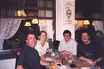 """June 17, 2002 - Hotel Restaurant 3 Könige & Post, Andermatt, Switzerland.  From left to right: Johann, Laura, myself and Karl. After departing my B&B in Andermatt that morning for a ride over the Klausenpass, the Pragelpass, the Ibereregg Pass and the Sattelegg Pass, I stopped at the post office in Andermatt to buy a Swiss phone card. As I'm parking, Johann, a rider whom I'd met and spent a day riding with in the Riva del Garda area during my 2000 Tour comes running up to me. """"What are you doing here, he asks in a surprised voice. """"The same thing you are, and that is riding some of the best roads in the world"""" I responded in German. After a short chat, we arranged to meet for dinner that evening. After a very tiring 320 kilometer day in the twisties, I rolled into Andermatt to fill up at the Shell station and who comes rolling up but a rider on a BMW R100 GS. Alright, my kind of girl, I'm thinking. She smiles a lot and waves to a tired and confused rider. It took fifteen or so seconds for it to click. It was Laura from Texas, the girl I had responded to on one of the motorcycle touring forums after she posted some questions about touring the Alps. In a nutshell she actually went through with her plans. She rented a motorcycle from Knopf Motorradreisen upon my recommendation and decided to take me up on my day or two offer as a tour guide which turned into five days. After I showed her to my B&B, we walked into town to meet with Johann and Karl (Johann's friend that joined him on this tour) for a much enjoyed get together over dinner and beer. A riding day doesn't get much better than this."""