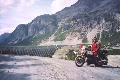June 13, 2002 - Lago di Cancano, Italy.  It may be a lake, but it is a dry one at that. Directly behind me, a steep drop off runs along the length of this road. Keep your eyes on the road as they say. Lago di San Giacomo is behind the dam pictured. The complete run up from Premadio around Lago di San Giacomo and back was approximately 40 kilometers of dusty gravel road. I met up with numerous large dump trucks coming from the quarry at the edge of Lago di San Giacomo. Needless to say, their tires rutted the hairpin corners.