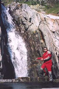 June 19, 2002 - Falls at the Rhone Gletscher parking lot on the Furka Pass, Switzerland.  It was very warm and the mist coming off this small waterfall at the edge of the parking lot was soothing. A day earlier, there was a wall of snow with an archway carved out so as to provide a view of these falls. The snow was melting fast.