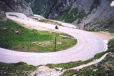 June 18, 2002 - St. Gotthard Pass, Switzerland.  There are three ways over the St. Gotthard Pass; the tunnel (boring), the newer road over the pass, and the original cobble stoned road pictured here with a rider enjoying its character. I drove over this pass back in 1996, but unfortunately at the time, this old cobble stoned road was closed and all I could do was look down upon it from the newer more direct road above. This section of road is about 1 kilometer south of the pass itself.