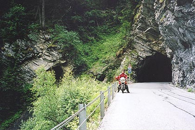 June 19, 2003 Along the Spissertal, Switzerland.   Immediately after the Swiss border crossing on the way to Samnaun, Switzerland, a sharp left turn takes one over a bridge, then through another Swiss border crossing and back down the more interesting side of the Spissertal though several tunnels carved into the side of the mountain high above the gorge. Traffic is light on this road which ends in Vinadi, Switzerland.
