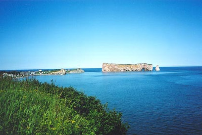 August 12, 2003 Percé, Quebec.  Percé lies on the eastern tip of the Gaspé peninsula. When the tide is low, one can take a walk over to that island in the photo. The coastal drive along route 132 from Rivière-du-Loup to Pointe-à-la-Croix, across from Campellton, New Brunswick, offers a great view of the St. Lawrence river, the Gulf of Saint Lawrence and the Baie des Chaleurs. Not to be missed, especially when the weather is as good as I was blessed with.