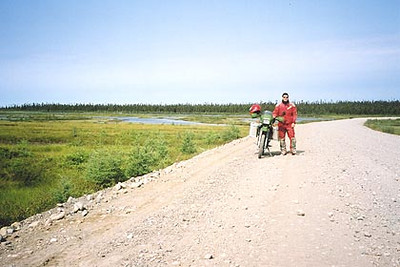 August 21, 2003 63 kilometers west of Churchill Falls, Labrador.  The Trans Labrador highway is pretty well straight as you've determined from the last few photos. There is the occasional elevation change, but as far as curves go, they are gentle at best. The best place to drive is the hard packed tracks made by cars and trucks, although it can be a bit rough at times due to potholes. If graders have smoothed the road out, it can be like driving on marbles. Driving itself isn't difficult but the constant concentration required to avoid larger rocks like the one ahead of me in the photo, can be very tiring. Speeds varied from as low as 50 km/hr to as high as 110 km/hr depending on the road surface. The majority of the time, 80 km/hr was an easy pace. Ego has no place here unless you don't mind being inconvenienced by a long wait for help.