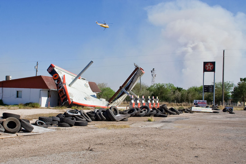 Wind damage to a service station, helicopter douses wild fires with water