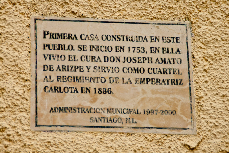 This plaque loosely translated is saying: First house constructed in Santiago. Beginning in 1753 the priest lived here and it served as regiment quarters for Empress Carlota in 1886.